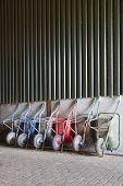 stock photo of wheelbarrow  - six old and rusty wheelbarrows rest against wall of farm barn - JPG