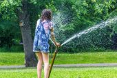 stock photo of sprinkler  - Children play with automatic sprinkler watering in garden in summer - JPG