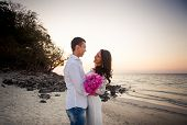 stock photo of barefoot  - brunette bride and handsome groom barefoot hug and laugh at sand beach at dawn - JPG
