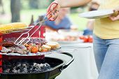 foto of frazzled  - Woman serving grilled steak on garden party - JPG