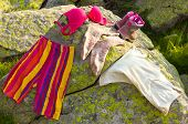 stock photo of lady boots  - Colorful ladies clothes on rocks close up - JPG