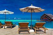 image of infinity pool  - Deck chairs with umbrella overlooking infinity pool and tropical lagoon - JPG