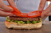 stock photo of hamburger  - Cook adding tomato on burger - JPG