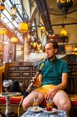 pic of shisha  - Man smoking turkish hookah in the cafe with coloful lamps on background in Istanbul - JPG