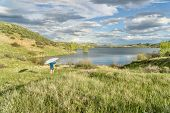 picture of horsetooth reservoir  - male paddler is carrying hi SUP paddleboard to a lake  - JPG