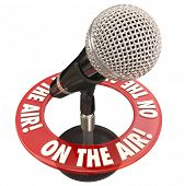 pic of interview  - On the Air words in a ring around a microphone to illustrate a live report or interview on radio or podcast program - JPG