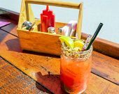 foto of bloody mary  - Caesar or bloody mary cocktail drink rimmed with spice and garnished with lime wedge pepper and olives on a hot summer day - JPG