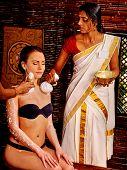 image of panchakarma  - Woman having ayurvedic massage with pouch of rice - JPG