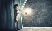 foto of curtains stage  - Young businesswoman opening stage curtain to another reality - JPG