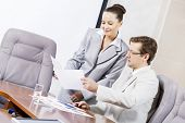 image of secretary  - Young attractive secretary showing boss business documents - JPG