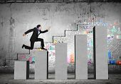 foto of step-up  - Young businessman stepping up on chart bar - JPG