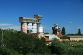 stock photo of silos  - Old factory with silo tanks for corn near river - JPG