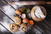 picture of pasta  - Raw homemade pasta and ingredients for pasta on wooden background - JPG
