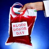 picture of hemostasis  - closeup of the hand of a doctor holding a blood bag with a sticker with the text blood donor day - JPG