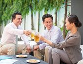 image of coworkers  - Coworkers drinking beer and chatting outdoors together - JPG
