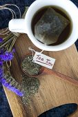 picture of tea bag  - hot tea cup with tea bag on wooden board with tea time tag - JPG