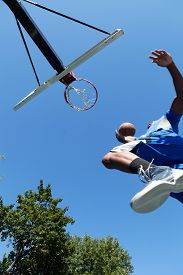 stock photo of slam  - Young basketball player driving to the hoop for a high flying slam dunk - JPG