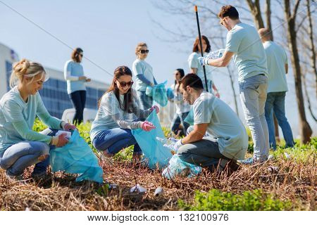 volunteering, charity, cleaning, people and ecology concept - group of happy volunteers with garbage