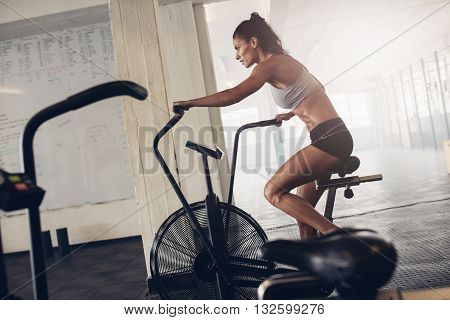 Fit Young Woman Using Exercise Bike At The Gym picture