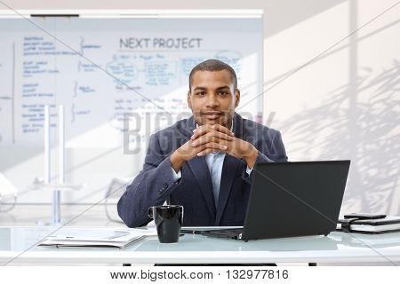 Afro american smiling confident businessman with laptop computer sitting at startup business office