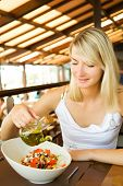 Beautiful young woman eating healthy vegetable salad in a restaurant