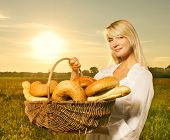 stock photo of household farm  - Beautiful young woman with a basket full of fresh baked bread - JPG