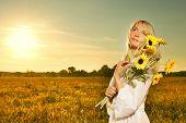 Постер, плакат: Молодая красивая женщина с букетом подсолнухи в поле на закате