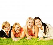 Group of happy friends lying on a green grass
