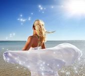 Blond woman with white shawl relaxing near the sea
