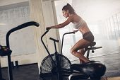Fit Young Woman Using Exercise Bike At The Gym poster