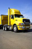 stock photo of semi-truck  - Yellow semi truck towing a load  - JPG