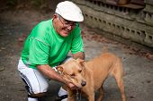 foto of happy dog  - An elderly Hispanic senior citizen man petting his dog with a large smile on his face - JPG
