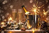New Years Eve celebration background with pair of flutes and bottle of champagne in  bucket  and a h poster
