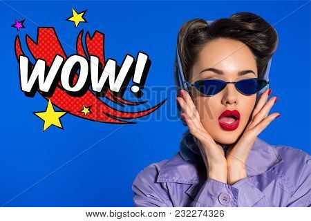 poster of Portrait Of Stylish Woman In Retro Clothing And Sunglasses With Comic Style Wow Sign Isolated On Blu