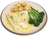 Baked haddock fillets in a lemon and herb sauce with vegetables.