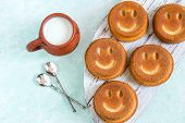 Funny Cupcakes In Form Of Smiling Face And Mug With Milk. Food That Causes Positive Emotions. Humoro poster