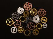 Group of different colorful cogwheels on a black background. Clockwork. Mechanical machinery. poster