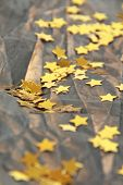 stock photo of gold glitter  - Golden stars on a brown crumpled paper - JPG