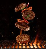 Pieces of minced meal for hamburgers flying above grill grid. Barbecue and grill poster