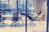 A time for relax. Young tired casual businessman relaxing at the desk in his office poster