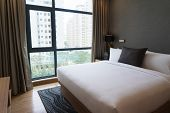 King size bed in hotel room. Modern comfortable bed with pillow and panoramic window with curtains in bedroom. City flat concept