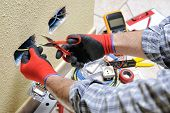 Electrician Technician At Work With Scissors On Cable In A Residential Electrical Installation poster