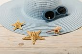 Beach Summer Concept. Blue Female Hat And Sunglasses On A Light Wooden Background. Selective Focus. poster