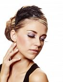 beautiful blond woman with long diamond false eyelashes and party hairstyle touching her neck over w