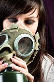Beautiful Girl Is Holding An Old Gasmask Against Dark Background