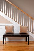 image of entryway  - A leather bench a pillows in an upscale home entryway - JPG