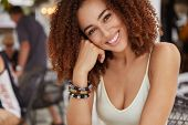 Close Up Shot Of Positive Glad Woman With White Teeth, Has Curly Dark Hair, Wears Fashionable Bracel poster