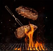 Flying beef steaks over flaming grill grid, isolated on black background. Barbecue and cooking poster