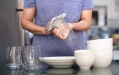 Woman Cleaning Product Concept Wiping Dishware Cleaner In Home And Kitchen poster