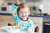 Adorable Baby Girl Eating From Spoon Vegetable Noodle Soup. Food, Child, Feeding And Development Con poster